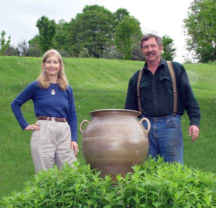 Christine and Robert standing next to large pot.