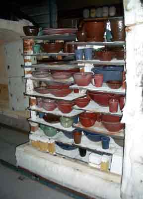 After the glaze firing and the kiln has cooled, it is opened and the copper red pots are now visible.